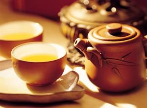 чайник и чашка с жёлтым чаем