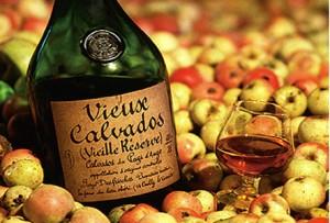 бутылка и бокал кальвадоса в яблоках